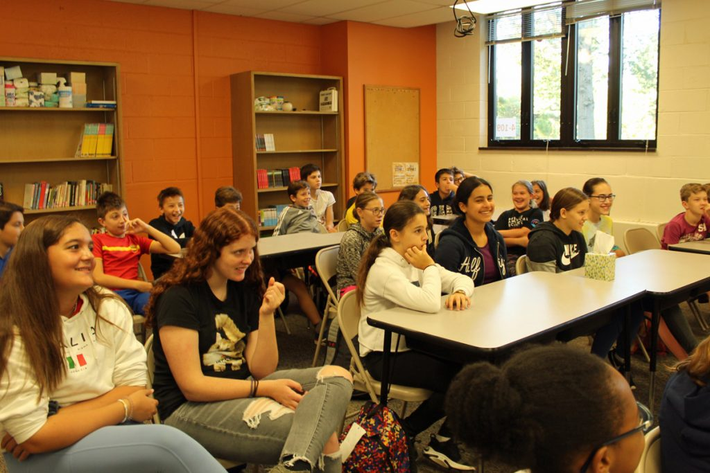 Middle school students sit and discuss the IB program
