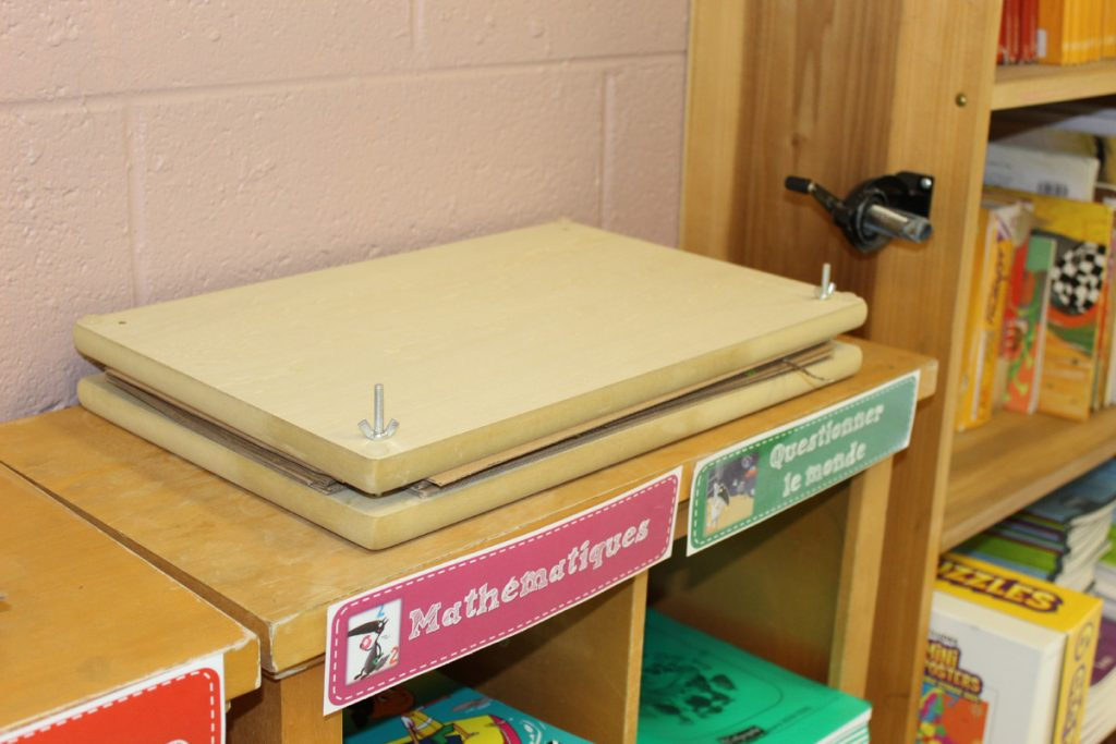 A leaf press sits on a cabinet within a classroom