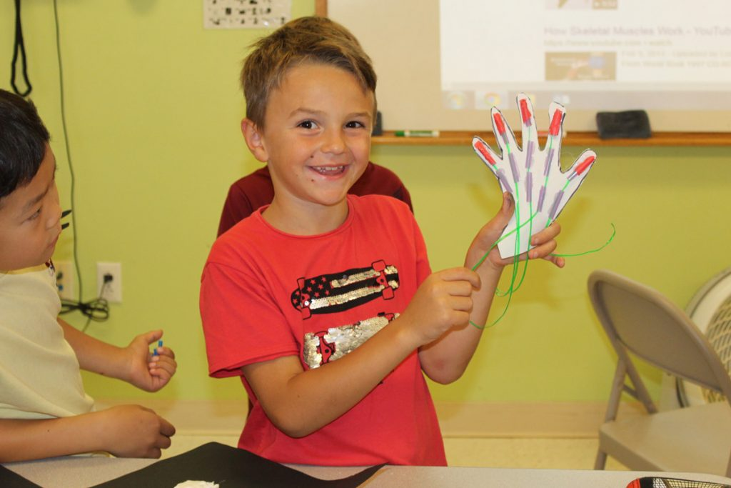 A student holds a skeleton hand made in class