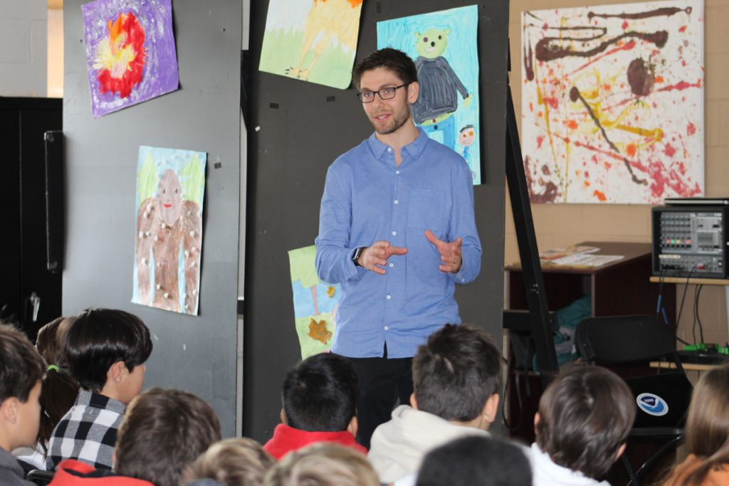 Scientist from the NOAA stands on stage in front of middle school students