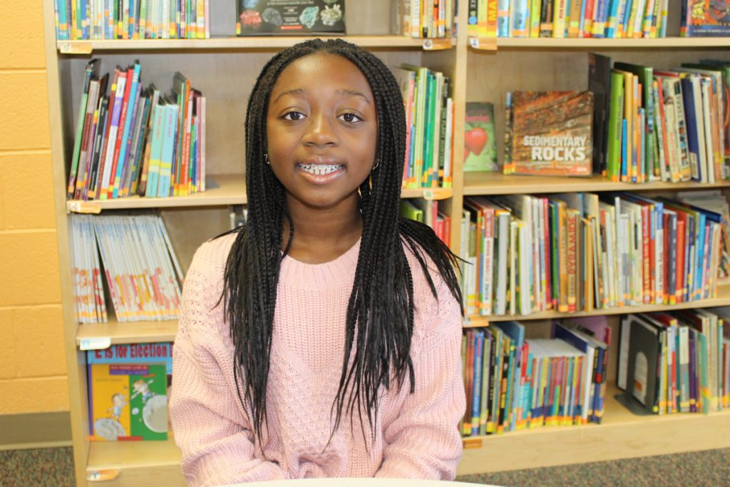 2019 alumni Zahra Lohoué sits in a library while she visits FASP to share her experiences.